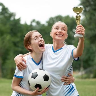Mulheres de tiro médio segurando o prêmio