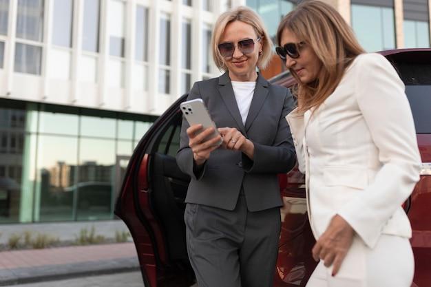 Mulheres de tiro médio segurando um smartphone