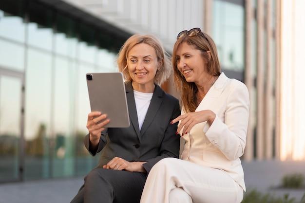 Mulheres de tiro médio segurando um tablet