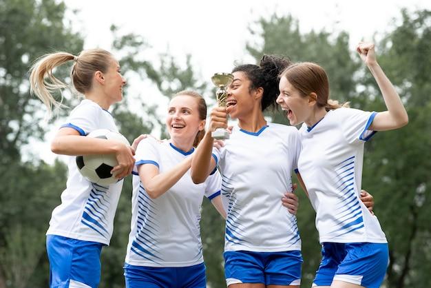 Mulheres de tiro médio segurando uma taça de ouro