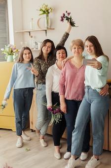 Mulheres de todas as idades segurando flores