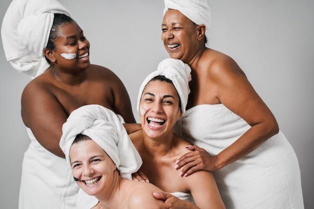 Mulheres de várias gerações com pele e corpo diversificados rindo juntos enquanto usam toalhas corporais - foco no centro do rosto feminino
