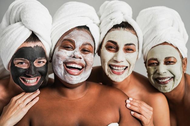 Mulheres de várias gerações se divertindo usando máscaras de beleza facial para terapia de cuidados com a pele - foco principal no rosto de uma garota africana