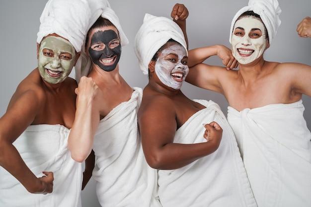 Mulheres de várias gerações se divertindo usando máscaras de beleza para a pele - foco principal no rosto de uma garota africana