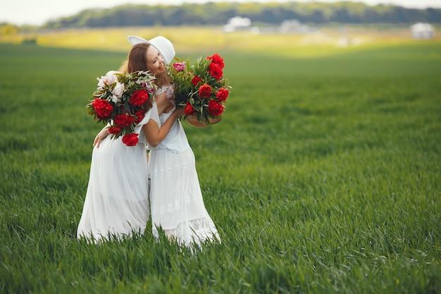 Mulheres de vestido elegante em pé em um campo de verão
