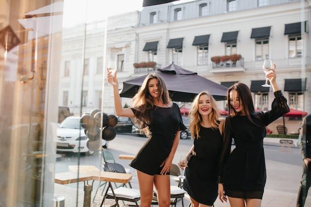 Mulheres de vestido preto com mangas compridas levantando taça de vinho e rindo