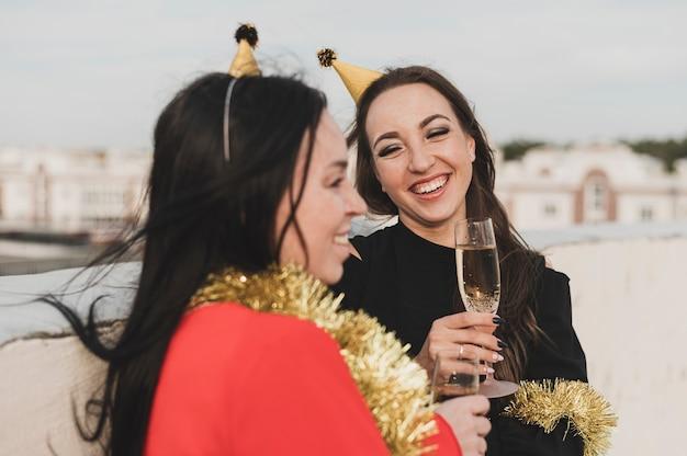 Mulheres de vestido vermelho e preto, sorrindo para a festa no telhado