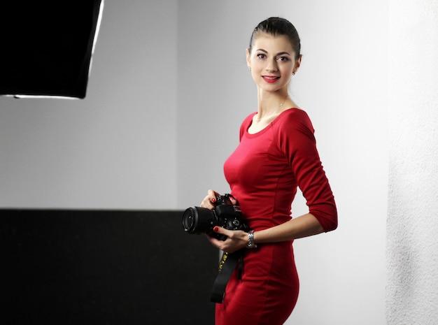Mulheres de vestido vermelho, mantendo a câmera profissional nas mãos