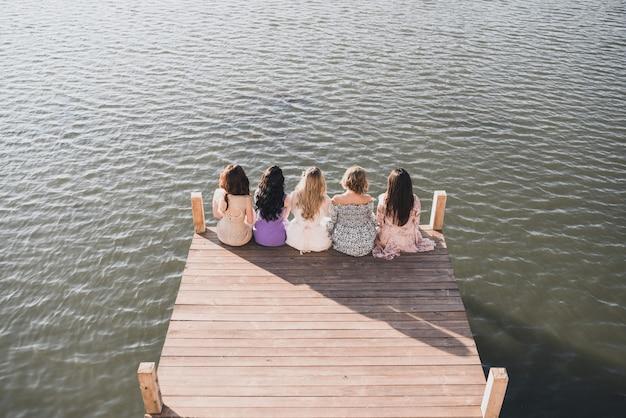 Mulheres de vestidos sentadas em uma alvenaria de madeira perto do rio