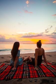 Mulheres deitadas na praia, aproveitando as férias de verão, olhando para o mar