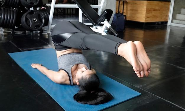 Mulheres deitadas no companheiro de ioga, fazendo exercícios abdominais.