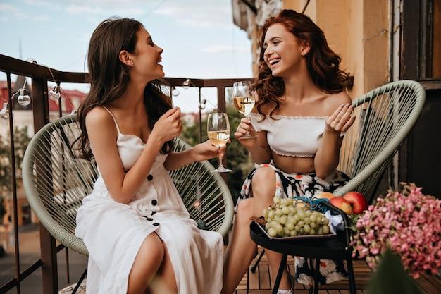 Mulheres descoladas conversam e apreciam vinho no terraço