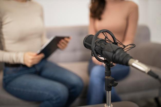 Mulheres desfocadas fazendo uma entrevista de rádio com microfone