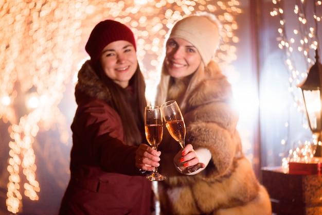 Mulheres desfrutando de champanhe. retrato ao ar livre de senhoras na luz