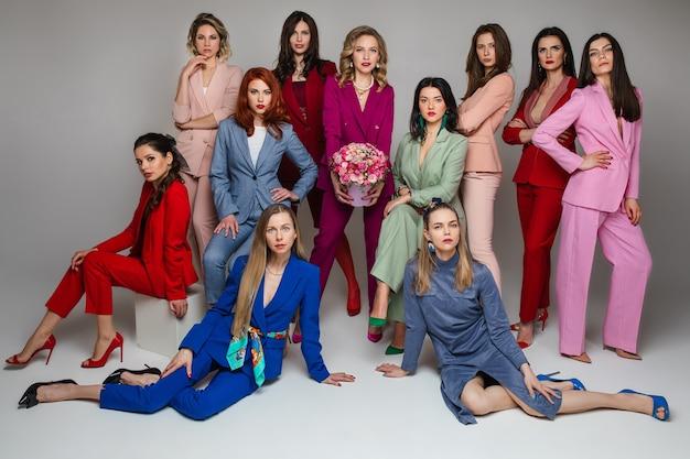 Mulheres deslumbrantes e elegantes em ternos da moda brilhantes e saltos altos posando juntas e olhando para a frente
