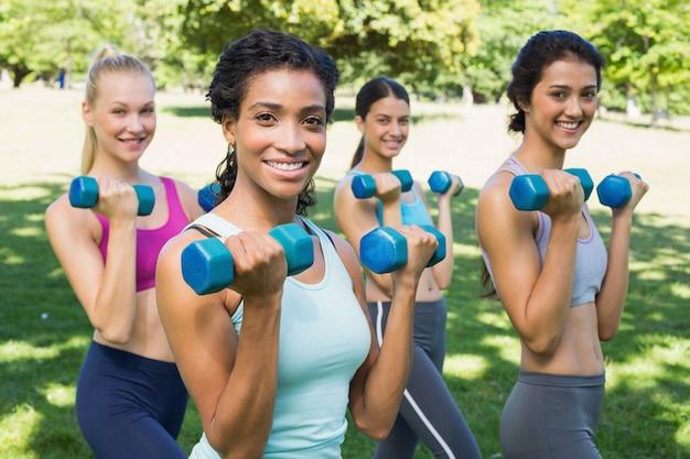 Mulheres desportivas confiantes, levantando pesos de mãos