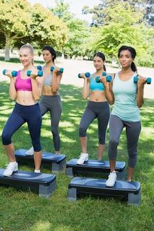 Mulheres desportivas fazendo ginástica aeróbica com halteres