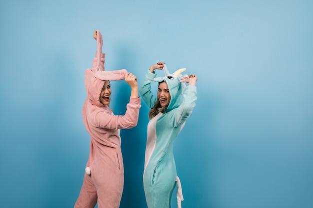 Mulheres despreocupadas engraçadas posando em kigurumi