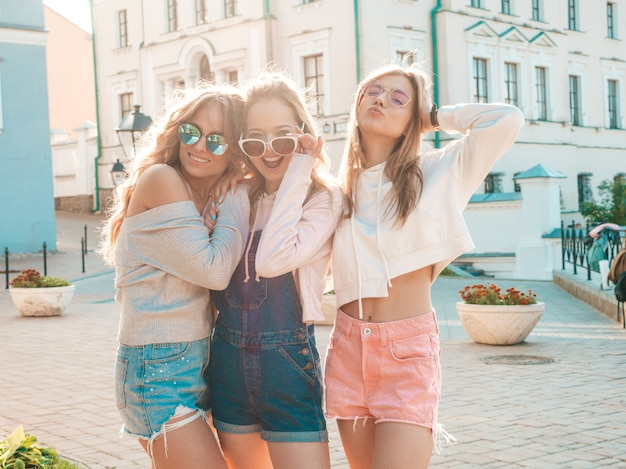 Mulheres despreocupadas sexy, posando no fundo da rua, abraçando ao pôr do sol