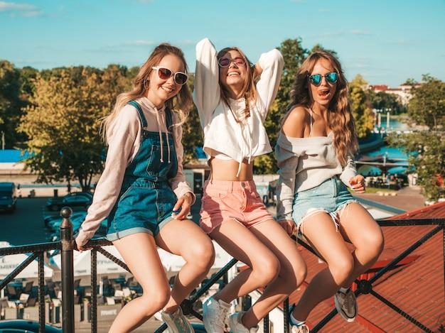 Mulheres despreocupadas sexy, sentado no corrimão da rua. modelos positivos se divertindo em óculos de sol