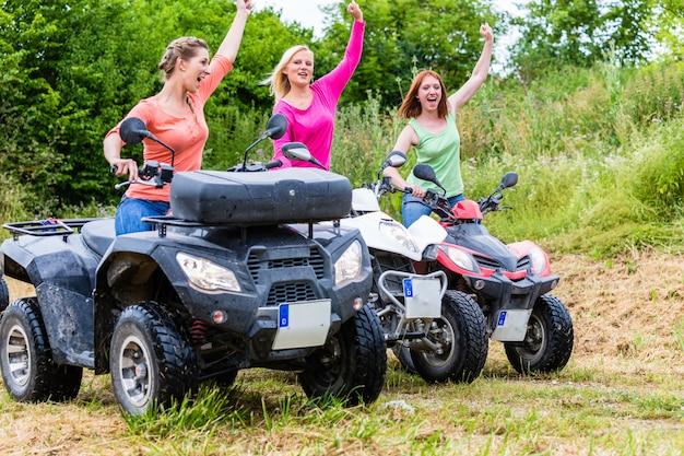 Mulheres dirigindo off-road com quad bike ou atv