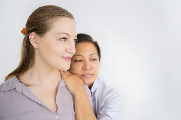 Mulheres diversas graves abraçando e olhando para longe