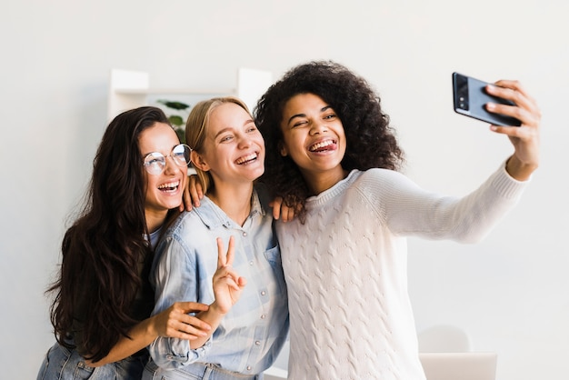 Mulheres do smiley no escritório que toma selfies