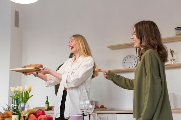 Mulheres do smiley que comem a pizza