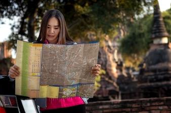 Mulheres do turista com Carregando uma trouxa Visualizando mapa, Sobre o templo em Ayutthaya.