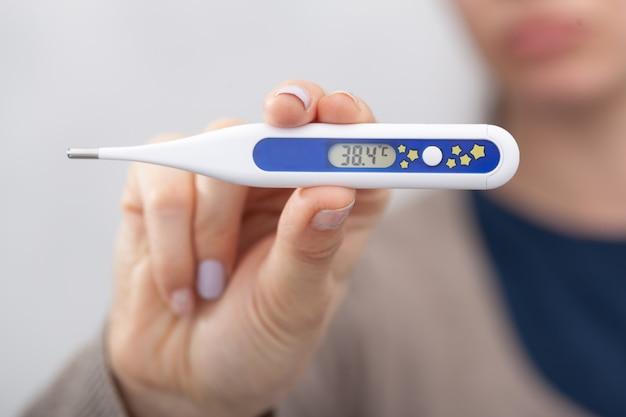 Mulheres doentes com um termômetro