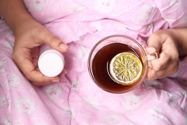 Mulheres doentes segurando chá de limão e pílula
