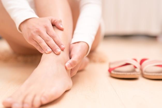 Mulheres dolorosas do tornozelo do pé que tocam no pé. conceito de saúde e médico