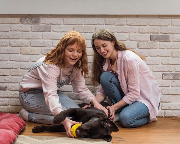 Mulheres e cachorro no chão.