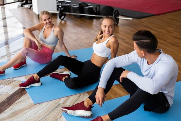 Mulheres e cara em tapetes de ioga