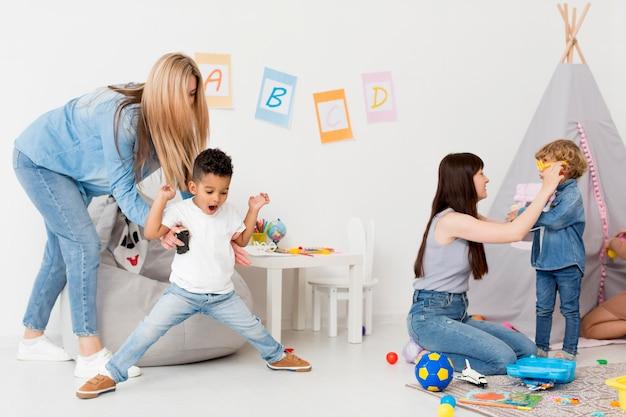 Mulheres e crianças em casa brincando