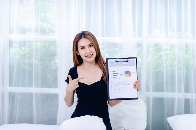 Mulheres e gráfico jovens mulheres de negócios apresentam planos de negócios