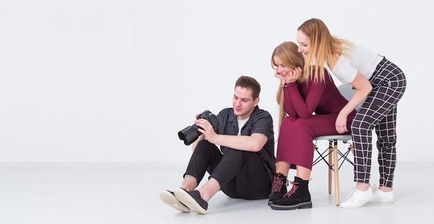 Mulheres e homem olhando fotos no estúdio e copie o espaço
