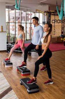 Mulheres e homem treinando na academia