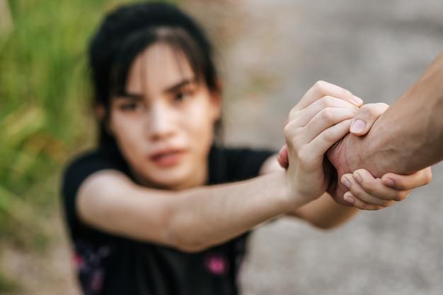 Mulheres e homens estão de mãos dadas para se exercitar.