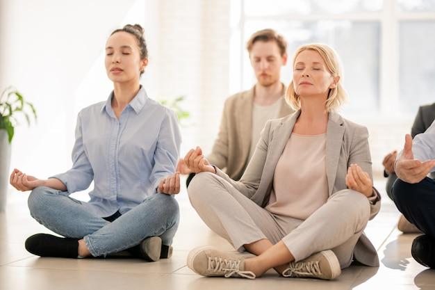 Mulheres e homens maduros e jovens em trajes casuais praticando exercícios de ioga no chão durante o intervalo