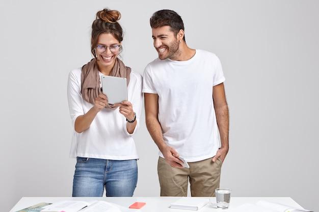 Mulheres e homens positivos assistem ao vídeo no tablet digital