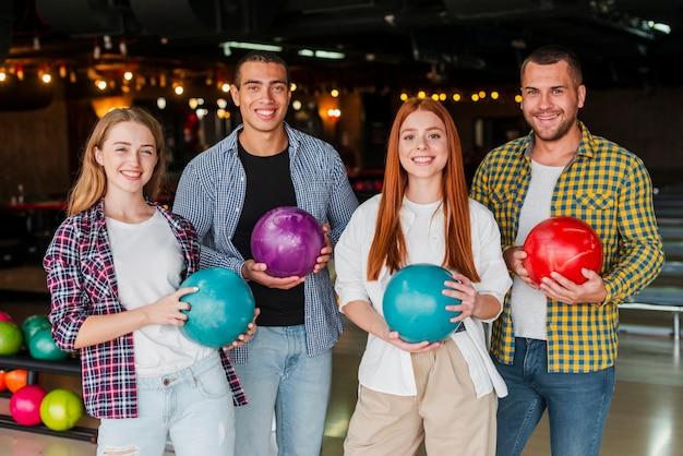 Mulheres e homens segurando bolas coloridas de boliche plano médio