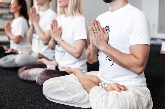 Mulheres e homens sentam-se em posição de lótus e meditam nas aulas de ioga. esportes de conceito e estilo de vida saudável.