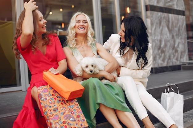 Mulheres elegantes com sacolas de compras em uma cidade