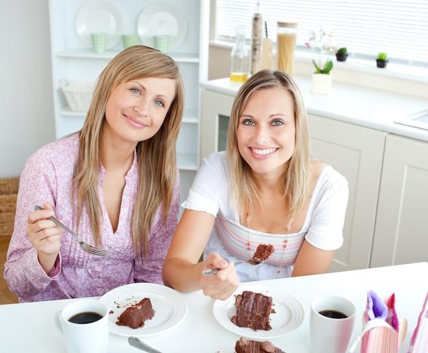 Mulheres elegantes comendo um bolo de chocolate durante o lanche na cozinha