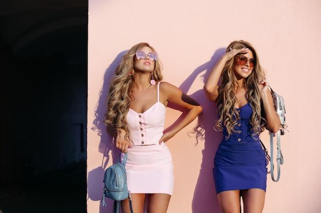 Mulheres elegantes e chiques, posando de óculos escuros e com bolsas azuis