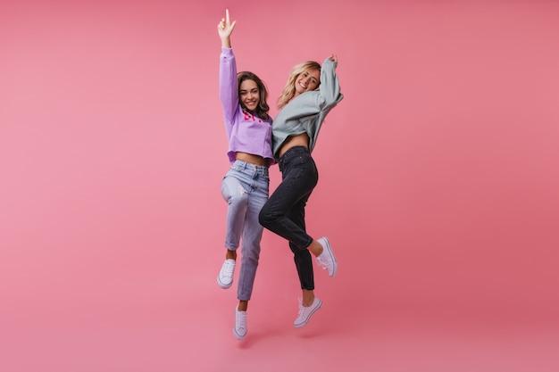 Mulheres elegantes e elegantes curtindo a vida. magníficas amigas pulando e acenando com as mãos.