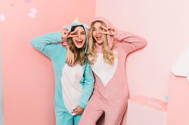 Mulheres elegantes em kigurumi em pé na parede rosa