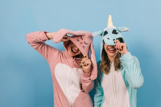 Mulheres elegantes em kigurumi juntas na parede azul