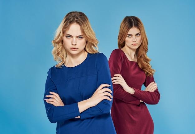 Mulheres elegantes em vestidos que comunicam emoções conflito de parede azul.